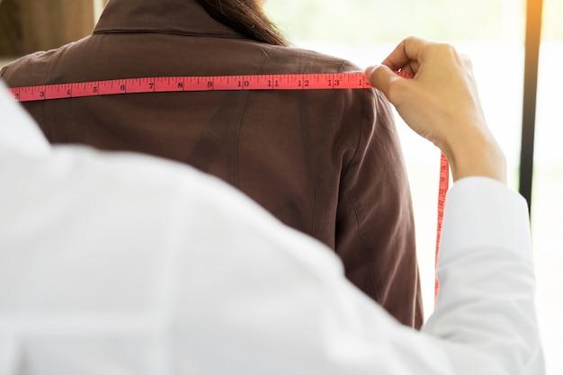 Créateur de mode mesurant sur la partie du corps des femmes pour une robe sur mesure pour une jeune fille d'affaires