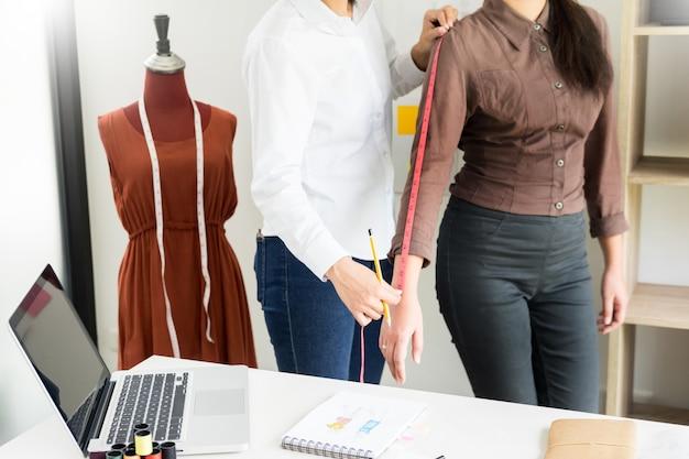 Créateur de mode mesurant sur la partie du corps des femmes pour une robe sur mesure pour un jeune