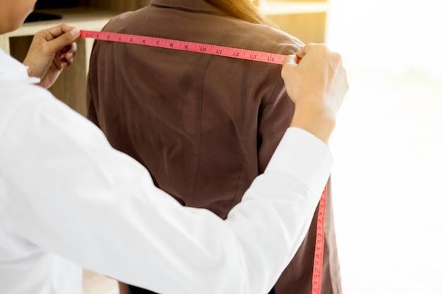 Créateur de mode mesurant la partie du corps des femmes