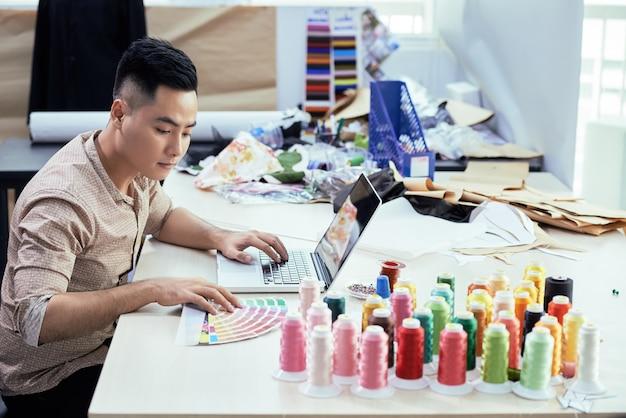 Le créateur de mode travaille sur la collection de la saison à venir, il choisit des fils de couleurs et o ...