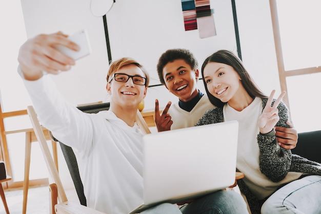 Créateur souriant faisant selfie avec des collègues.