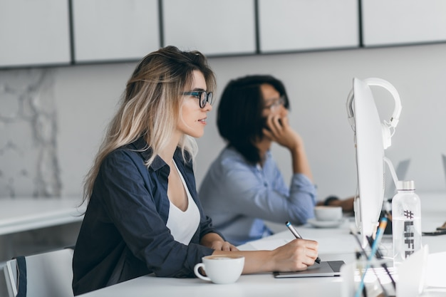 Créateur web indépendant inspiré utilisant une tablette et un stylet, regardant l'écran pendant que son amie parlait au téléphone. étudiant asiatique tenant un smartphone et en tapant sur le clavier, assis à côté d'une fille blonde.