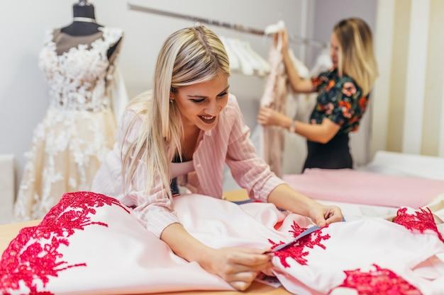 Les créateurs de mode travaillant dans un salon pour coudre des robes de mariée.