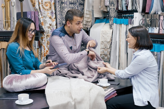 Créateurs, vendeurs de tissus travaillant dans la salle d'exposition