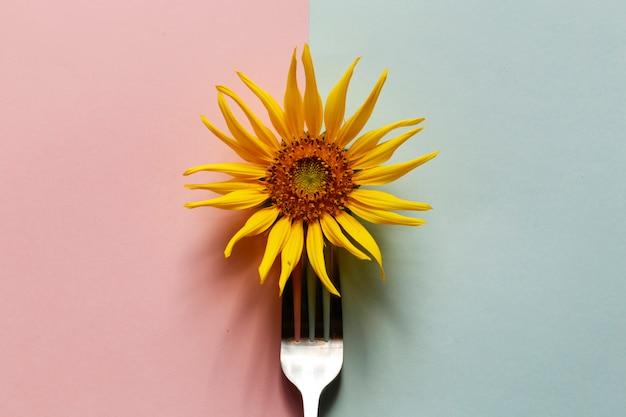 Créatif de tournesol avec une fourchette en acier inoxydable sur rose pastel et bleu