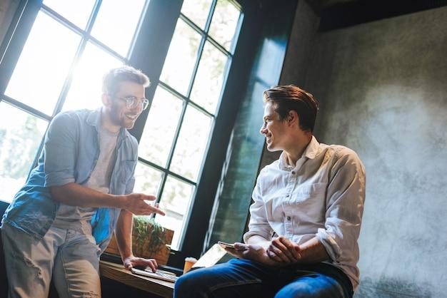 Créatifs ayant une réunion informelle à une table dans un studio de design tourné de professionnels