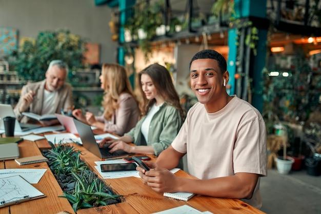 Des créatifs multiraciaux dans un bureau moderne. un groupe de jeunes gens d'affaires et un patron senior travaillent avec un ordinateur portable, une tablette, un téléphone intelligent, un ordinateur portable, des graphiques. une équipe performante en coworking