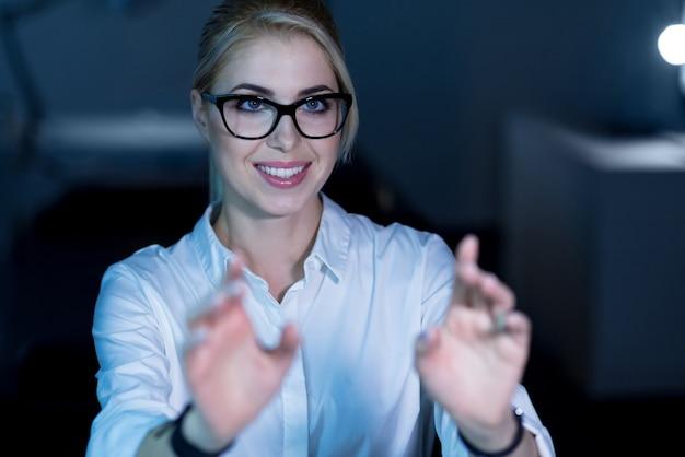 Création d'un nouveau langage de programmation. femme informatique expérimentée et talentueuse positive assise au bureau et utilisant les technologies futures tout en travaillant sur le projet