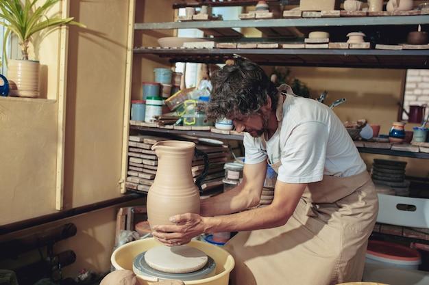 Création d'un pot ou d'un vase d'argile blanche en gros plan. maître pot. mains d'homme faisant macro de cruche d'argile. le sculpteur dans l'atelier fabrique une cruche en gros plan en faïence. tour de potier tordu.