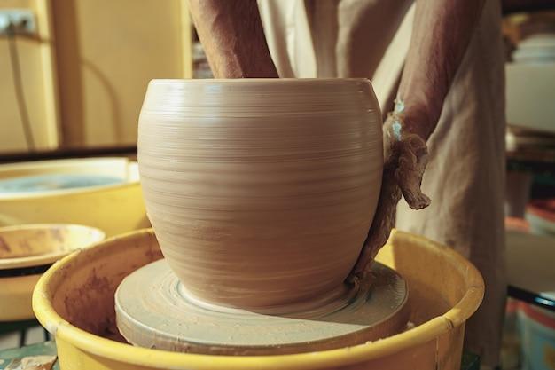 Création d'un pot ou d'un vase d'argile blanche en gros plan. maître pot.