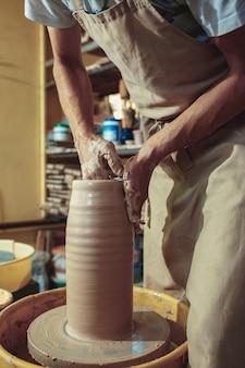 Création d'un pot ou d'un vase en gros plan d'argile blanche. maître crock. mains d'homme faisant macro cruche d'argile.