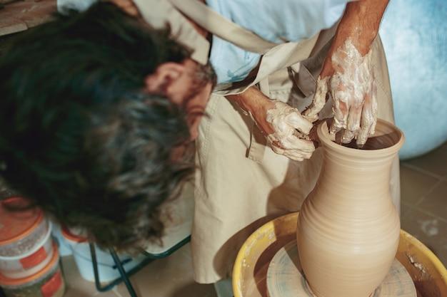 Création d'un pot ou d'un vase en gros plan d'argile blanche. maître crock.