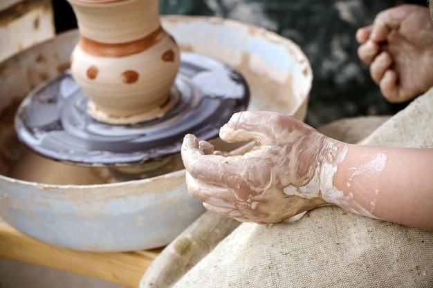 Création d'un vase d'argile blanche en gros plan.