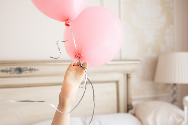 Creative child petits pieds détient bouquet de ballons roses anniversaire beige intérieur maison aux couleurs claires