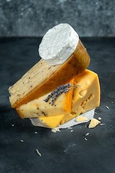 Creative différentes sortes de fromage portant sur fond sombre avec espace de copie. camembert, fromage aux épices, fromage hollandais. grande affiche pour la fromagerie. contexte alimentaire. flou sur la lavande