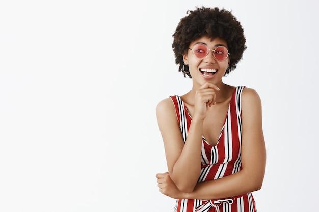 Créative et élégante femme designer afro-américaine féminine en salopette à la mode à rayures et lunettes de soleil roses tenant la main sur le menton souriant et regardant à gauche avec intérêt