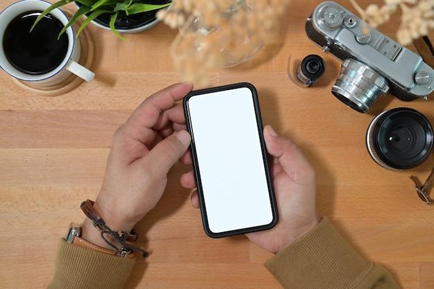 Creative main élégante tenant un téléphone mobile à écran blanc