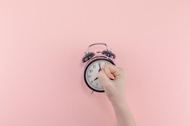 Creative plat laïque matin temps émotions concept vue de dessus de la main de femme tenant un réveil vintage noir fond de papier de couleur rose millénaire pastel avec copie espace modèle de style minimal pour le texte