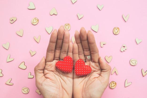Creative plat poser des mains de la femme avec deux coeurs sur fond pastel.