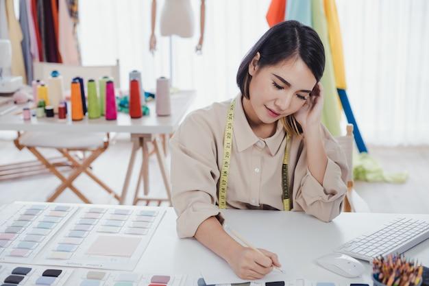 Une créatrice asiatique réfléchit et conçoit des vêtements pour les clients qui commandent des articles au bureau de créateurs du studio.