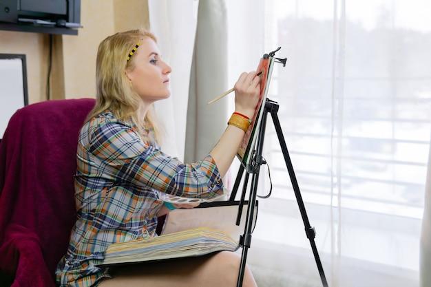 La créatrice dessine une illustration sur un chevalet
