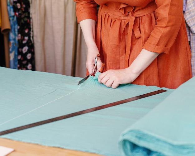 Créatrice de mode féminine ou coupe de tissu sur mesure sur table avant de coudre des vêtements en atelier