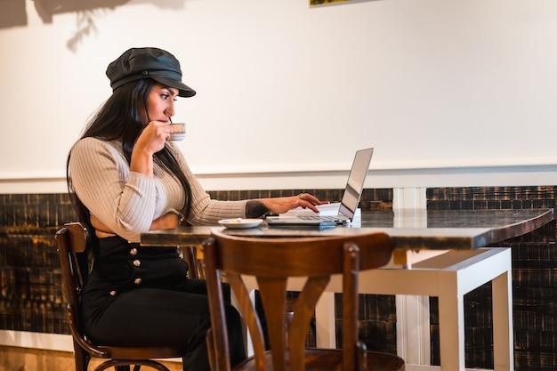 Créatrice de mode latine faisant des créations dans une cafétéria avec son ordinateur portable, prenant un café