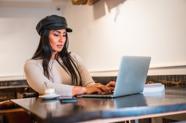 Créatrice de mode latine faisant des dessins dans une cafétéria avec son ordinateur portable
