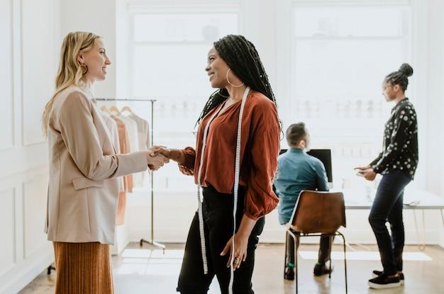Créatrice de mode serrant la main de son client