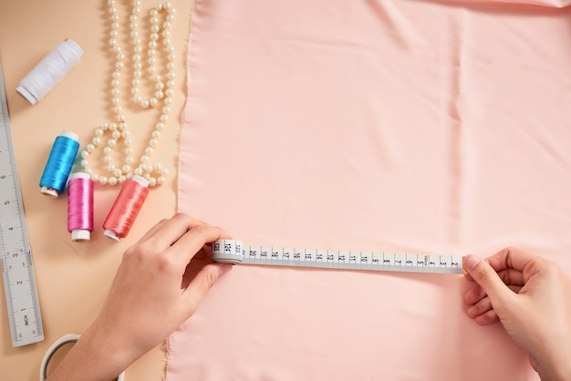 Créatrice de mode, tailleur de femme posant sur son lieu de travail avec du tissu coupé