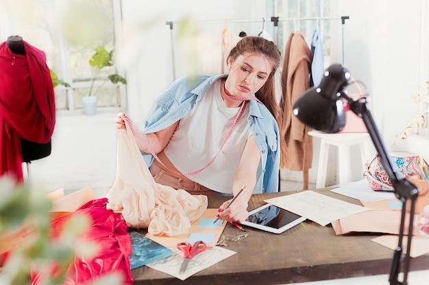 La créatrice de mode travaillant en assis sur le bureau
