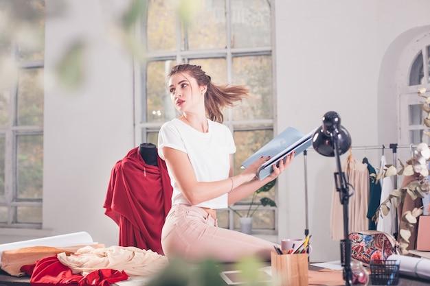 La créatrice de mode travaillant en studio assis sur le bureau
