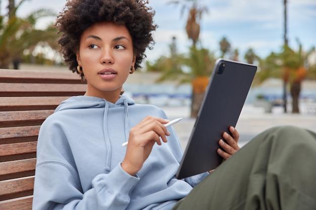 Une créatrice pensive tient une tablette avec un stylet utilise une connexion internet publique pour créer des croquis médiatiques via une application pour un artiste créatif habillé avec désinvolture sur des poses de banc en bois à l'extérieur