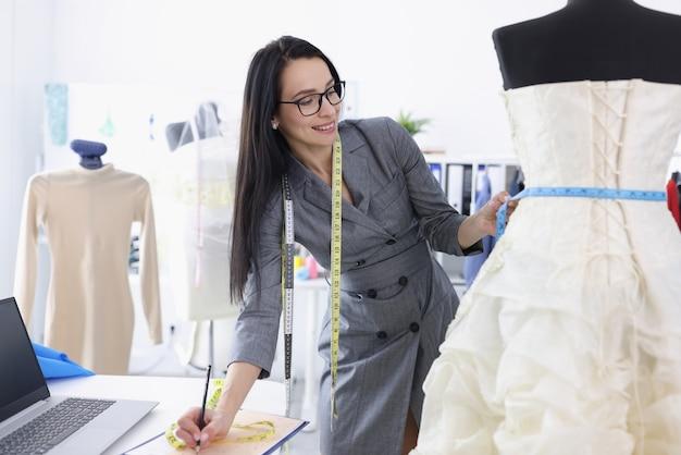 La créatrice prend des mesures de la robe de mariée sur le mannequin. salon de couture de mariage