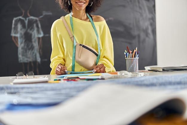 Une créatrice de vêtements pour femme afro-américaine avec un ruban à mesurer et un sac de ceinture contient des feuilles de papier colorées
