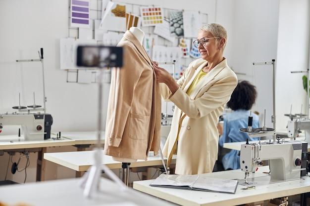 Une créatrice de vêtements pour femme mûre travaille avec une veste en filmant une vidéo tandis qu'une couturière afro-américaine en