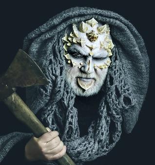 Créature diable avec peau de dragon et barbe homme avec hache à la main tête de démon avec capuche grise sur le visage de monstre noir aux yeux blancs épines et verrues concept d'horreur et de mort
