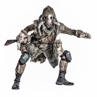 Créature post-apocalypse dangereuse et mystérieuse, survivante d'une catastrophe écologique mondiale en lambeaux, masque à gaz, portant une amulette mystique, accroupie avec une machette sanglante dans les mains isolée sur un tournage en studio blanc