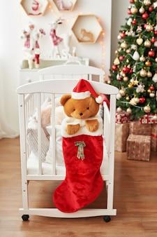 Crèche de noël, décoration de noël dans la chambre des enfants, salle de jeux pour enfants décorée pour le nouvel an, chambre des enfants blanche. jouets et cadeaux de noël dans la chambre des enfants, lit blanc avec des peluches