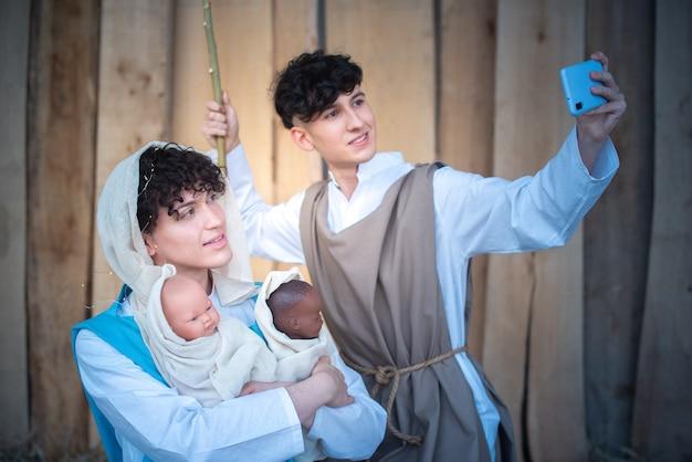 Crèche de noël où deux androgynes prennent un selfie avec un mobile