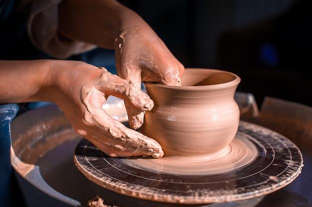 Créer un pot ou un vase. maître pot. faire une cruche en argile. le sculpteur dans l'atelier fabrique une cruche en gros plan en faïence. tour de potier. concept de poterie.