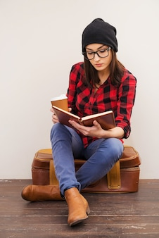 Créer un réconfort autour d'elle. belle jeune femme en chapeaux tenant un livre et une tasse de café alors qu'il était assis sur une valise