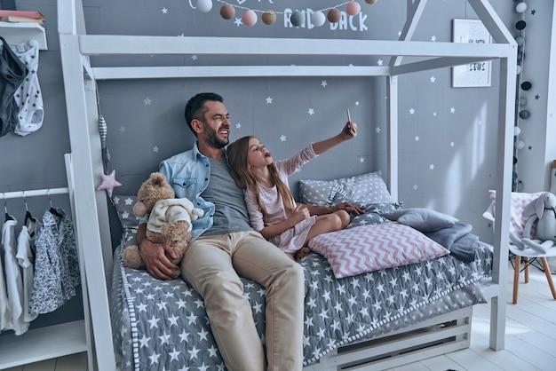 Créer des souvenirs heureux. jeune père et sa petite fille prenant le selfie