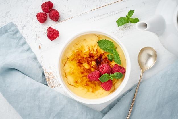 Crema catalana, dessert espagnol avec baies en ramequin blanc, vue de dessus, recette de carte de fond