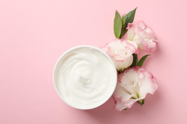 Crème et belles fleurs sur fond rose, espace pour le texte