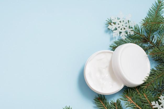 Crème blanche avec arbre de noël et flocons de neige sur fond bleu, fond. soins du corps d'hiver