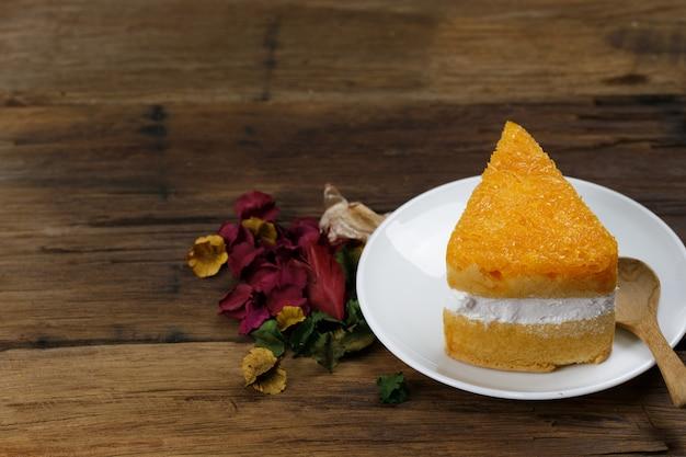 Crème de boulangerie sur soucoupe blanche sur le plancher en bois.