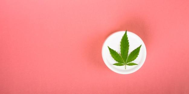 Crème cosmétique au cannabis sur fond rose à plat avec espace de copie.