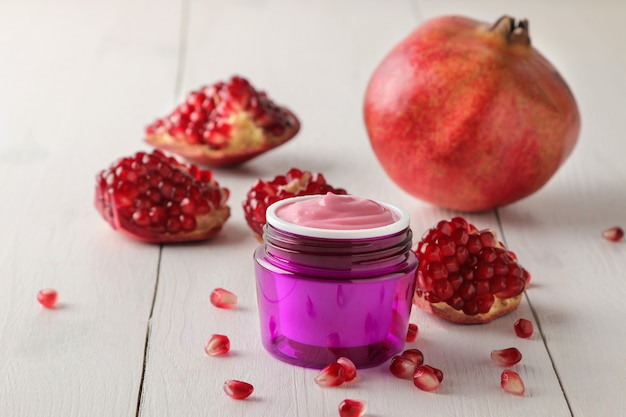Crème cosmétique dans un pot lilas et à la grenade fraîche sur une table en bois blanc.