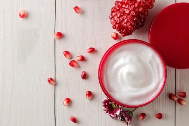 Crème cosmétique dans un pot rouge avec des fleurs et de la grenade fraîche sur une table en bois blanc.